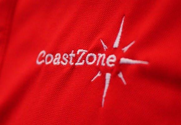Nærbillede af bluse med CoastZones logo