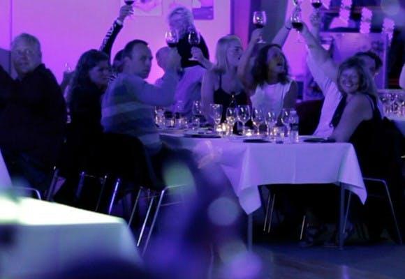 Mennesker ved et bord med hvid dug som løfter armene i skål til en sommerfest