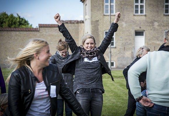 Smilende mennesker og i midten en kvinde med hænderne over hovedet som fejrer sin succes i teambuildingaktiviteten Viljens Vej