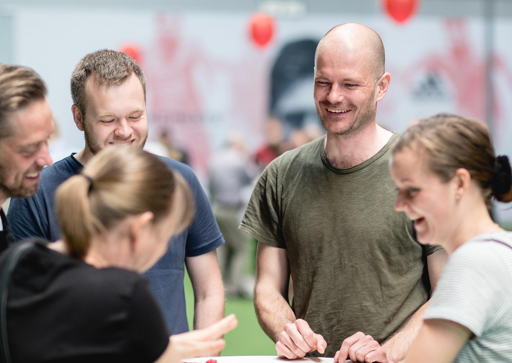 Fem medarbejdere samlet rundt om et bord til et firmaarrangement i København