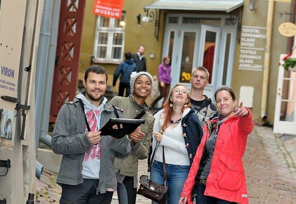 Et team a fem personer på en brostensgade hvor de er i gang med teambuildingaktiviteten Urban Experience