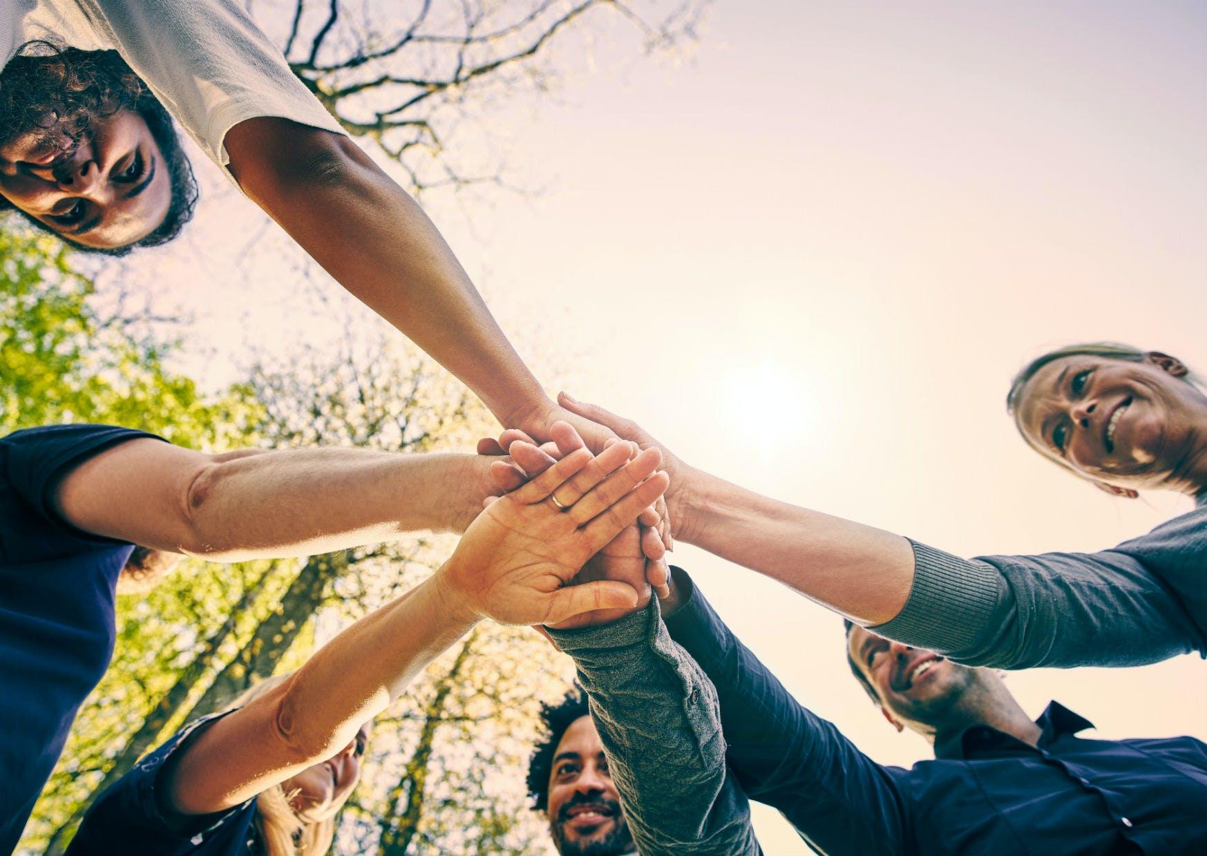Fem personer samler hænderne til kampråd i forbindelse med teambuilding