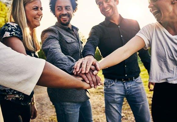 Fem glade mennesker samler hænderne til kampråb efter succesfuld teambuilding aktivitet