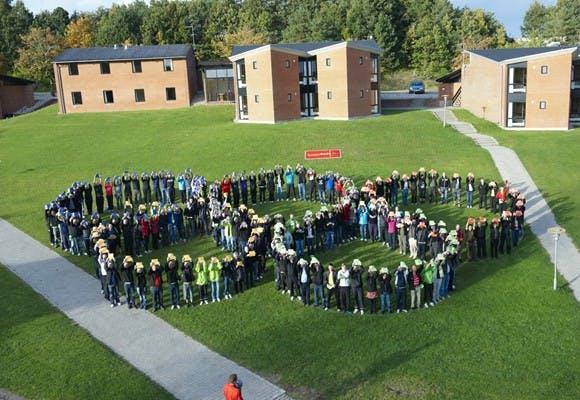 Et par hundrede mennesker der sammen danner formationen af logoet for De Olympiske Lege