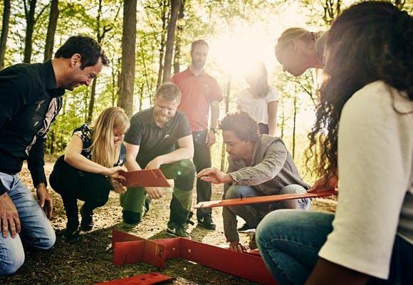 I en skov i Jylland er en gruppe mennesker i færd med at samle performance puzzle som er en udendørs teambuilding aktivitet
