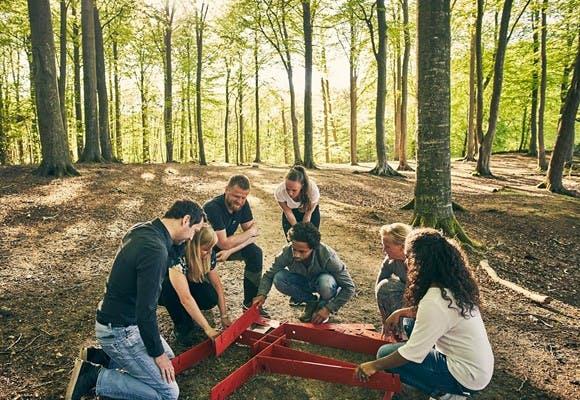 Syv mennesker i en skov løser en samarbejdsøvelse i forbindelse med teambuildingaktiviteten CoastZone Challenge