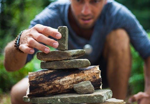 Mand stabler sten oven på hinanden som billede på balanceret lederudvikling