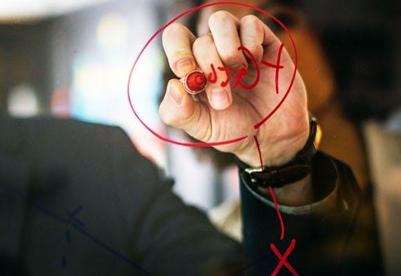 Hånd der skriver med en rød tusch under planlægning af HR årshjul