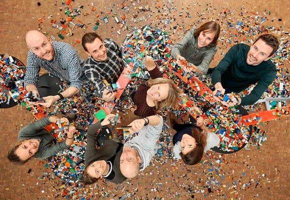 Foto oppefra af ni glade medarbejdere med konfetti, som fejrer den positive udvikling af deres samarbejde